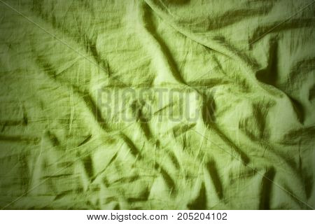 Green cloth surface. Crumpled sheet with dark lines