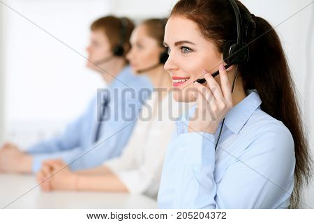 Call center operators. Focus at brunette business woman in headset