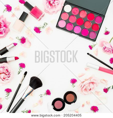 Feminine desk with woman cosmetic and pink flowers on white background. Flat lay, top view. Beauty background for woman