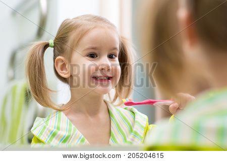Cute child kid girl brushing teeth and looking in mirror in bathroom