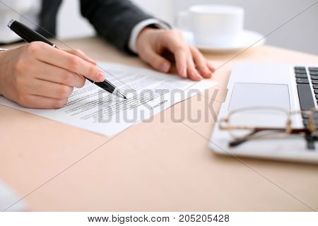 Business woman ready to sign a contract while sitting at the table