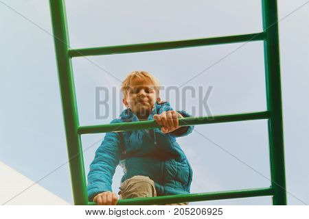 little boy playing on monkey bars at playground outdoors