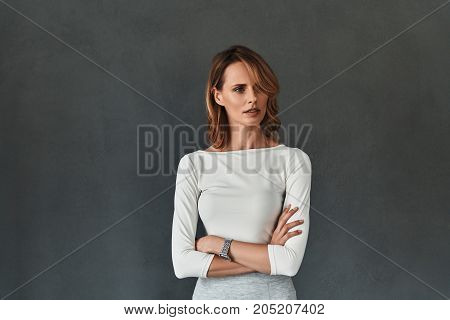 Young expert. Thoughtful young woman in smart casual wear keeping arms crossed and looking away while standing against grey background