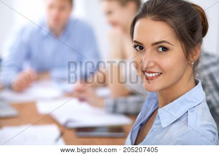 Beautiful business woman on the background of business people during meeting. Casual clothing style.