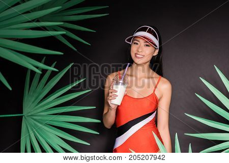 Woman In Swimsuit And Visor Drinking Milkshake