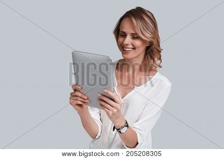I am online! Beautiful young woman looking at digital table and smiling while standing against grey background