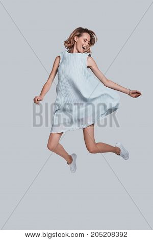 Going crazy. Full length of playful young woman smiling while jumping against grey background