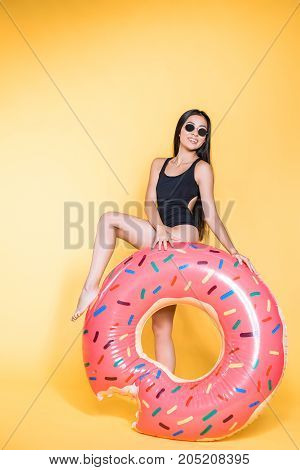 Woman In Swimsuit With Doughnut Pool Float