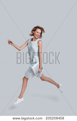 Mid-air motion. Full length of playful young woman gesturing and smiling while jumping against grey background