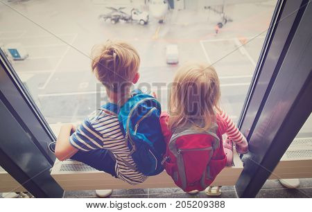 little boy and girl looking at planes in airport, family travel
