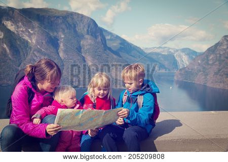 mother with kids travel in Norway looking at map