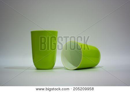 Two mug of plastic. Two green mug of plastic. Isolate on white background.