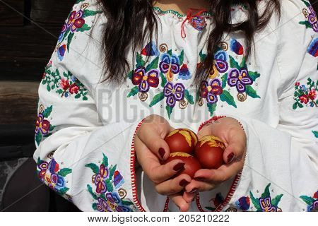 Girls hands holding eggs. Young girl in traditional embroidered blouse holding eggs. Easter eggs offered by girl.