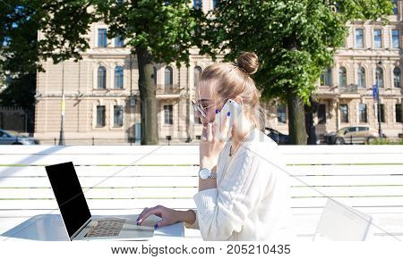 Young woman smart student talking on mobile phone during work on portable laptop computer. Hipster girl learning via notebook and having cell telephone conversation. Using net-book and cellphone