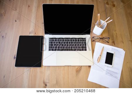 Modern workplace with contemporary laptop computer with touch bar, digital tablet and smart mobile phone. Desktop with portable open notebook, touch pad and cell telephone. Paper documents on table