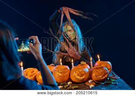 Girl capturing photo of Halloween costume woman with pumpkins with her smart phone