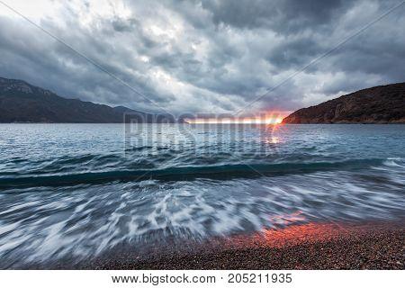 Sun Setting Under Storm Clouds At Bussaglia Beach In Corsica