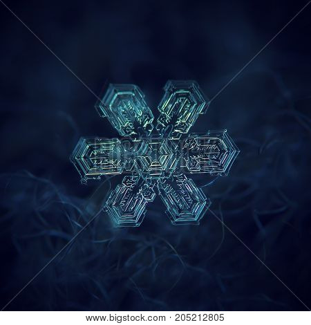 Real snowflake at high magnification. Macro photo of large star plate snow crystal with six broad arms, big central hexagon and complex inner pattern. Snowflake glittering on dark blue background.