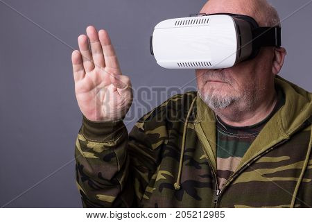 Senior Man In Wearable Technology Vr Glasses. Confident Old Man Wearing Camouflage Clothing In Virtu