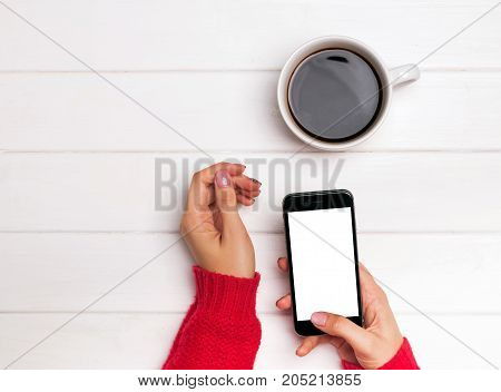Woman's Hands In Red Sweater Holding Smartphone With Blank White Screen.