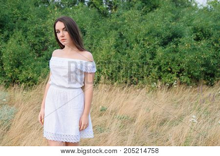 Portrait Of A Young Beautiful Girl In A Park In White Dress