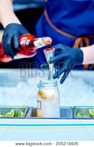 Bartender Is Pouring Alcohol From A Measuring Glass Into A Glass