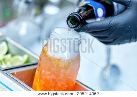 A Plastic Glass Of Cocktail On Ice. The Barman Pours A Glass Of