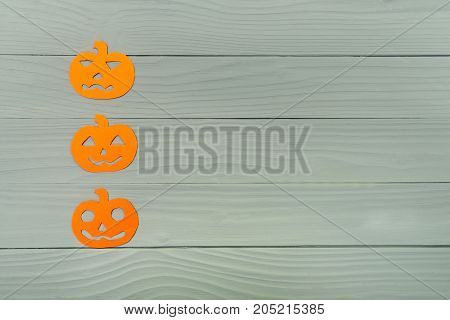 Top view of paper silhouette of three different pumpkin left vertically on grey wooden background. Halloween holiday background. Copy space