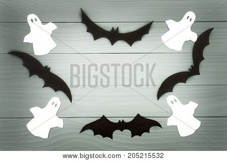 Halloween holiday background made of frame with bats and ghosts cut paper on gray board. Copy space. Light up