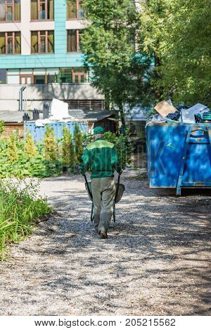 Elderly worker in uniform with a trolley near the garbage container