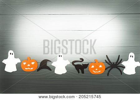 Halloween holiday background with pumpkins, cat, spider, hat and ghosts cut paper on gray board. Copy space. Light up