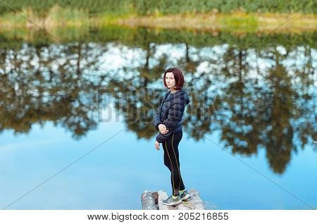 Portrait of sporty beautiful adult brunette woman the fall city park posing near blue lake with autumn trees reflections. Warm cloudy weather. Outdoors lifestyle.