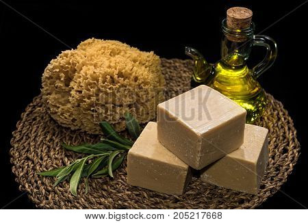 Handmade olive oil soaps together with a natural sea sponge and a bottle of olive oil on natural matting
