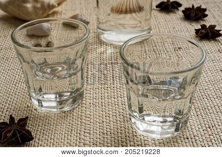 Glasses and bottle of traditional drink Ouzo or Raki on natural matting
