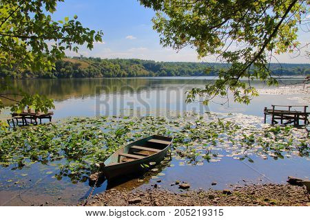 The picture was taken in Ukraine on the South Bug River on a summer day. In the photo the old boat is moored to the shore of a quiet river overgrown with water lilies.