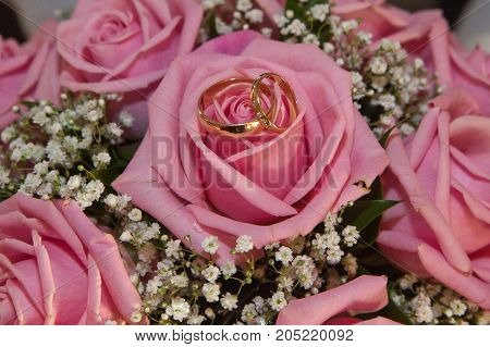Wedding Wedding Rings And Bouquet Of Pink Roses.