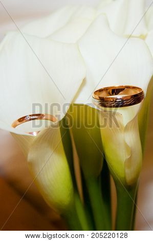 Wedding Wedding Rings And A Bouquet Of White Lilies.