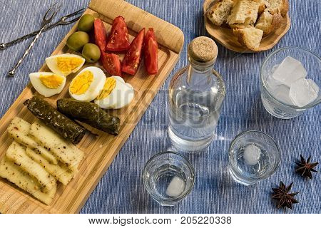 Two glasses and a bottle of traditional drink Ouzo or Raki and appetizers on natural matting