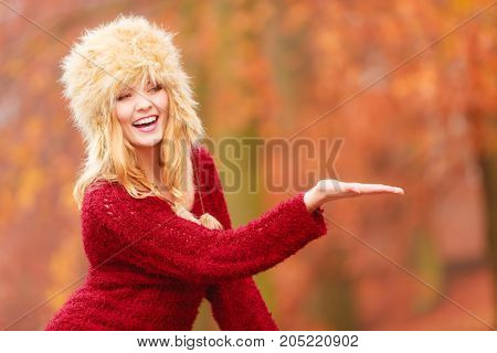 Portrait of pretty smiling woman in fall forest park with open empty palm hand for copy space. Happy gorgeous young girl in fur winter hat and sweater. Autumn fashion.