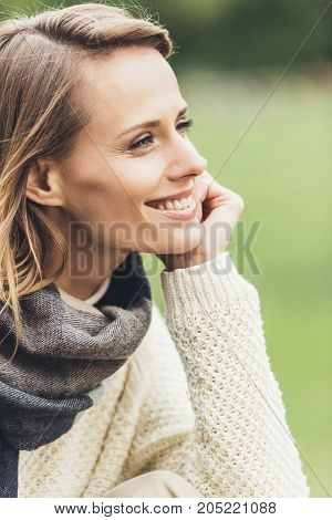 portrait of attractive smiling stylish woman looking away