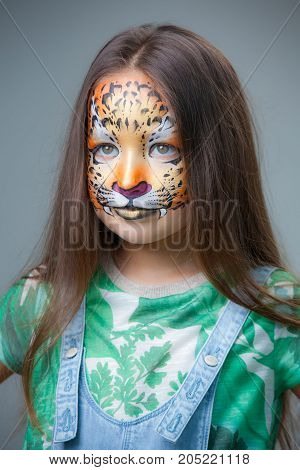 beautiful girl with a painted tiger on her face on a gray background close-up