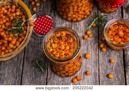 Berries of sea buckthorn with syrup in glass on a wooden background. Selective focus.