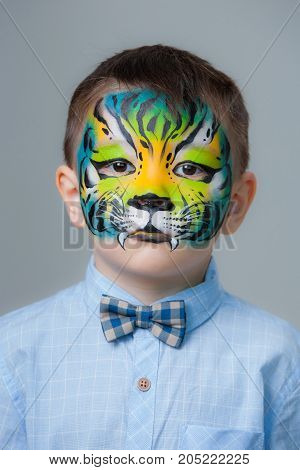 little boy painted like a tiger on a gray background. face painting
