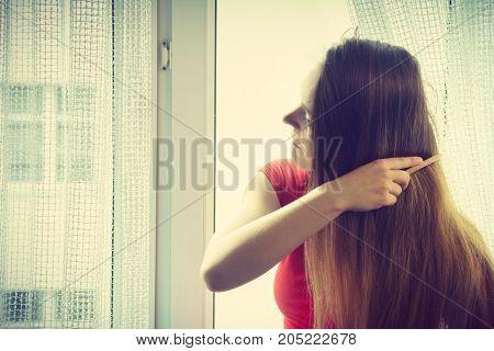 Woman Sitting On Windowsill Brushing Her Hair