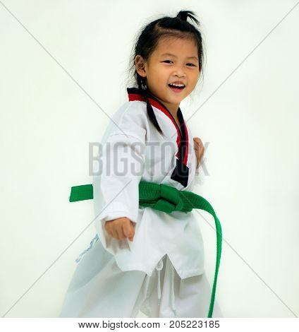 Asian girl wearing white Taekwondo suit acting ready to battle On white background.