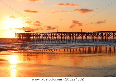 Golden sunrise over the ocean. Atlantic ocean landscape with a wooden pier in Myrtle Beach area South Carolina USA.