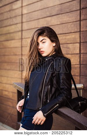Outdoor portrait of a pretty teenage girl with wooden planks wall as a background