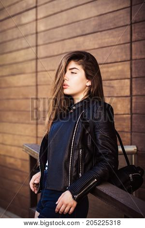 Outdoor portrait of a pretty teenage girl with hair covering her face and with wooden planks wall as a background