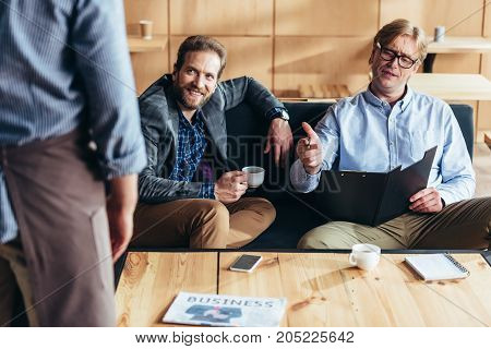 Businessmen Drinking Coffee In Cafe