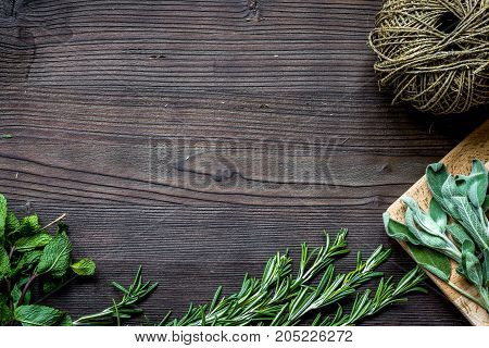 fresh herb frame of rosemary and thyme on dark wooden background top view